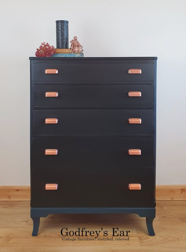 Black painted chest of five drawers with copper and dark blue legscup handles