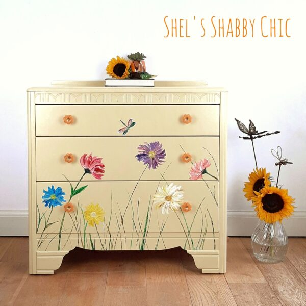 A mid-century 3 drawer chest of drawers in a mellow yellow. Hand painted with wildflowers, grasses and a solitary dragonfly. Stylish bedroom storage.